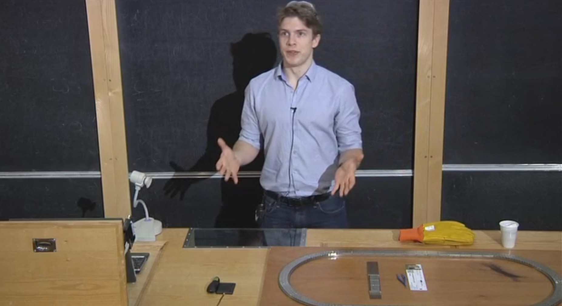 young researcher giving a talk in front of a blackboard with magnets