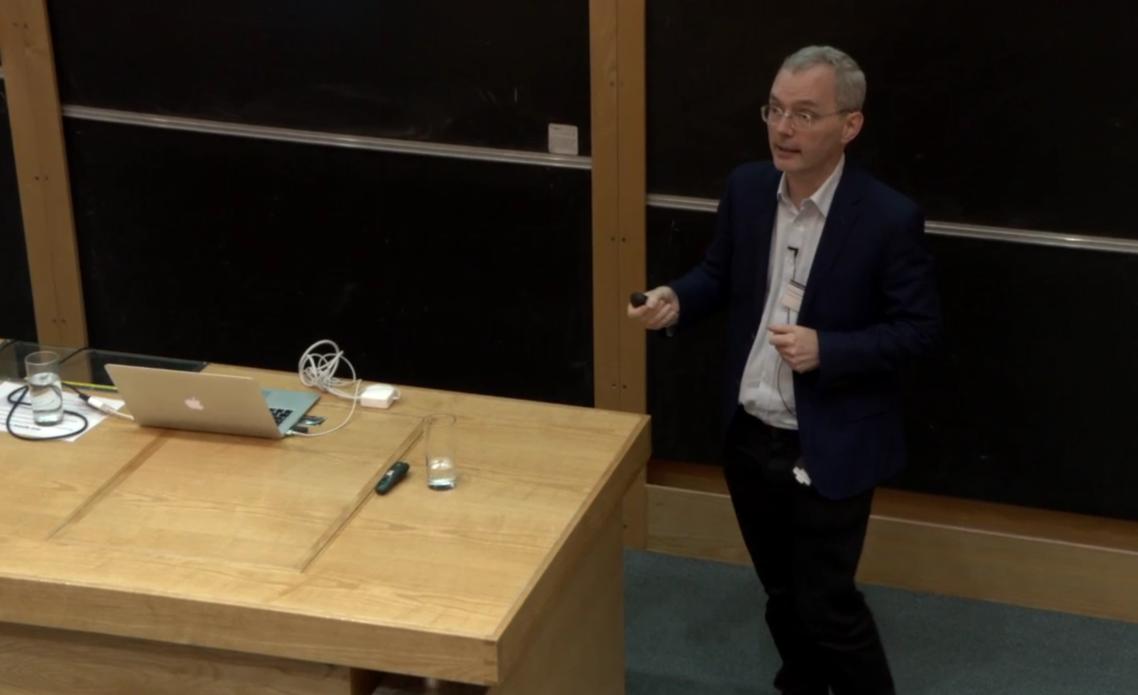 Male professor talks at front of lecture theatre