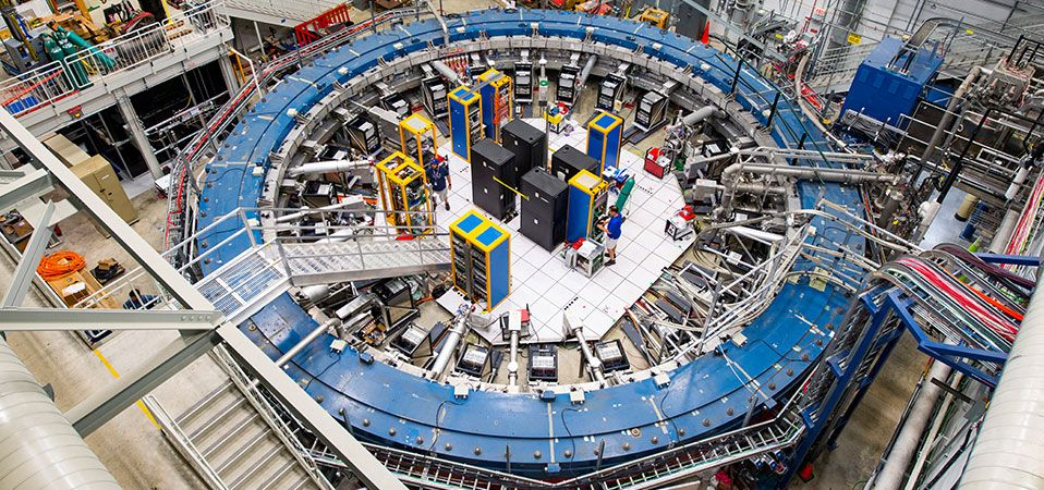 The Muon g-2 ring sits in its detector hall amidst electronics racks, the muon beamline, and other equipment.
